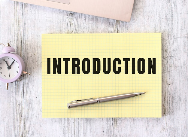 Introduction text written in a notebook lying on a wooden work table next to a laptop