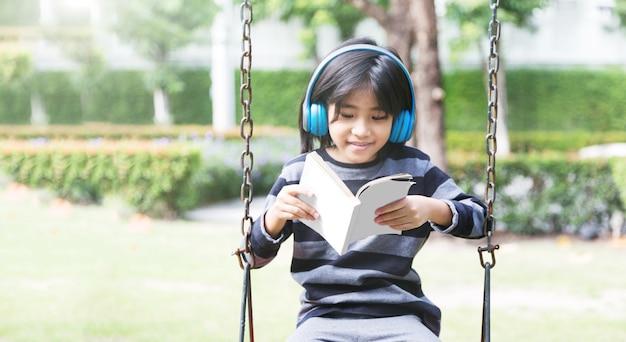 イヤホンの音楽に満足し、公園で一人でいるアジアの子供たちのデジタル世代の考え方を内向的に