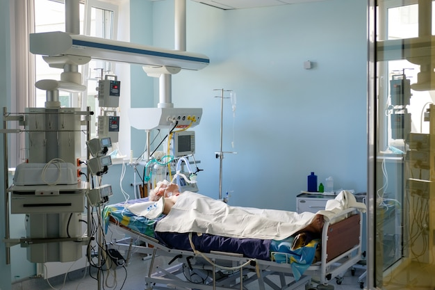 중환자 실에서 혼수 상태에 누워있는 avl에서 삽관 된 성인 백인. 위험 상태에있는 환자.
