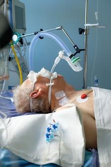 중환자 실에서 혼수 상태에 누워있는 avl에서 삽관 된 성인 백인