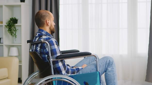 車椅子に座っている無効な落ち込んでいる若い男。