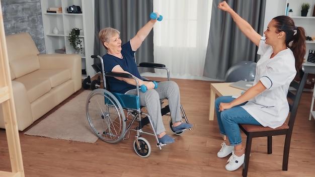医者と回復療法をしている車椅子の無効な祖母。障害のある障害のある老人が専門家の助けを借りて看護師を回復し、リタイヤメントホームの治療とリハビリテーションを行う