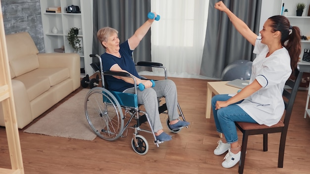 Invalid grandmother in wheelchair doing recovery therapy with doctor. disabled handicapped old person recovering professional help nurse, nursing retirement home treatment and rehabilitation