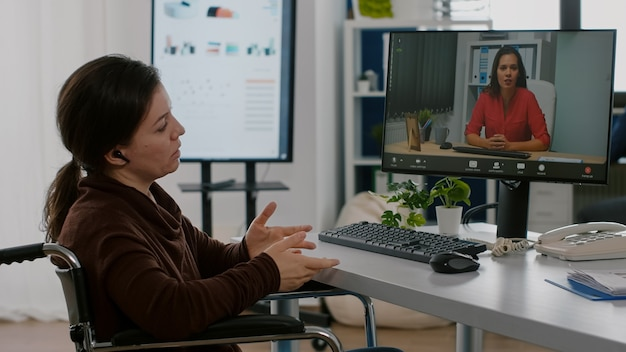 職場の車椅子に座っている金融プロジェクトのスタートアップオフィスで働くヘッドセットを使用してビデオ会議中に議論している無効な障害者起業家