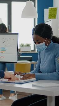 一緒に働いている保護マスクを持つ無効な男性とアフリカの従業員