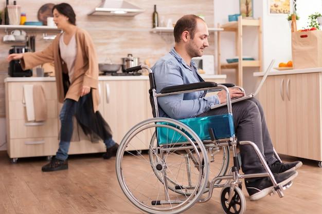 냉장고 앞에 서 있는 동안 부엌에서 원격으로 노트북 작업을 하는 휠체어를 탄 장애인. 사고 후 통합 보행 장애가 있는 장애인 마비 장애인.