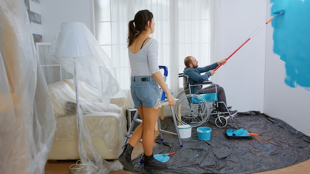 Invalid man painting wall while sitting in wheelchair. handicapped, disabled ill and immobilizes man helping with apartment redecoration and home construction while renovating and improving.