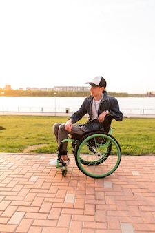 Invalid man sitting on a wheel chair and enjoying a walk outdoors high quality photo