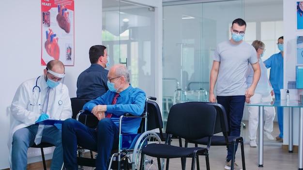 Старик-инвалид в маске против заражения коронавирусом в инвалидной коляске обсуждает с врачом в зоне ожидания больницы. медсестра, приглашая пациента в смотровую.