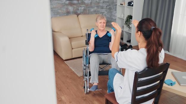 医師のサポートを受けてリハビリトレーニングを行っている車椅子の無効な老婆。障害のある障害のある老人が専門家の助けを借りて看護師を回復し、リタイヤメントホームの治療とリハビリテーションを行う