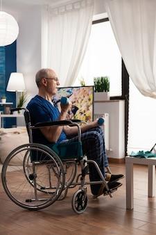 거실에서 근육 저항 훈련을 하는 팔 운동을 연습하는 운동 아령을 들고 휠체어를 탄 무능한 노인. 태블릿에서 온라인 운동 코스를 보고 있는 연금 수급자