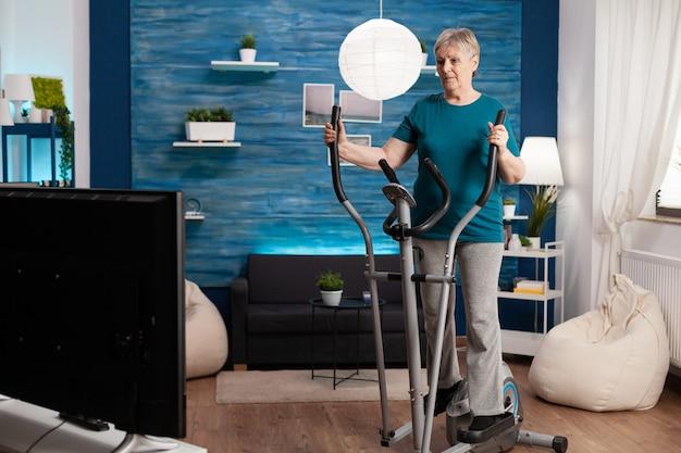 体重を減らすためにリビングルームのサイクリングバイクマシンでエアロビクスをしている無効な年配の女性。脚の筋肉運動をしているテレビでオンライン有酸素運動ビデオを見ている退職年金受給者