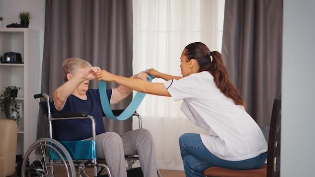 医者の助けを借りてリハビリをしている車椅子の無効な年配の女性。トレーニング、スポーツ、回復とリフティング、老人ホーム、ヘルスケア看護、健康サポート、社会的支援、