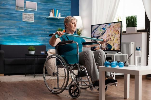タブレットでトレーニングビデオを見ている障害事故後に回復している体の筋肉を伸ばす抵抗弾性バンドを保持している車椅子の無効な年配の女性