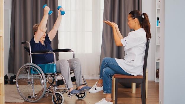 看護師とのリハビリテーション中にダンベルで車椅子トレーニング中の無効な年配の女性。トレーニング、スポーツ、回復とリフティング、老人ホーム、ヘルスケア看護、ヘルスサポート、社会