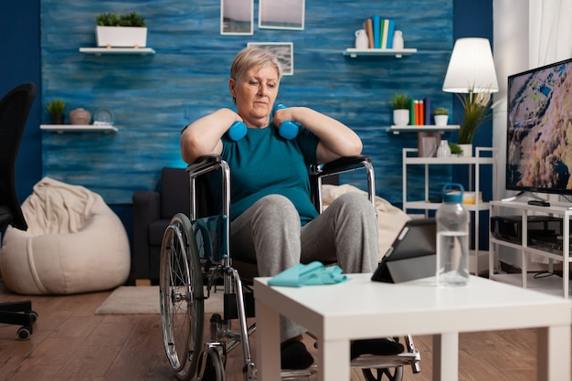거실에서 태블릿으로 체육관 신체 운동을 보고 있는 휠체어를 탄 잘못된 노인 여성