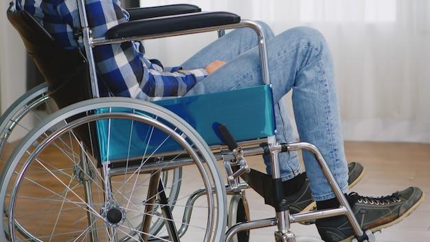 窓に迷子に見える車椅子の無効な思慮深い男。