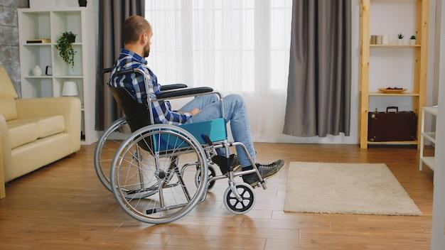 無効な若い男と車椅子で落ち込んでいます。