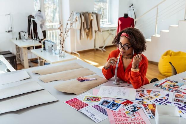 새로운 모습을 창조합니다. 패션 스튜디오에 머물면서 자신의 작업에 대해 생각하는 관심이있는 잘 생긴 짙은 피부의 여성