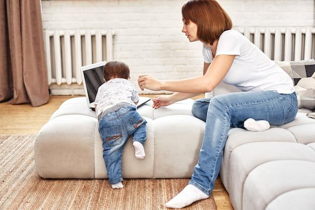 朝のマルチタスクの子供を持つ発明の現代の母親。ママと赤ちゃんは現代のテクノロジーとガジェットです。流用で自宅で働きます。