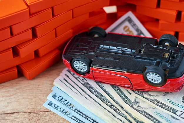 Inverted car on pile of a dollar bills.  concept of car insurance, damages after the accident