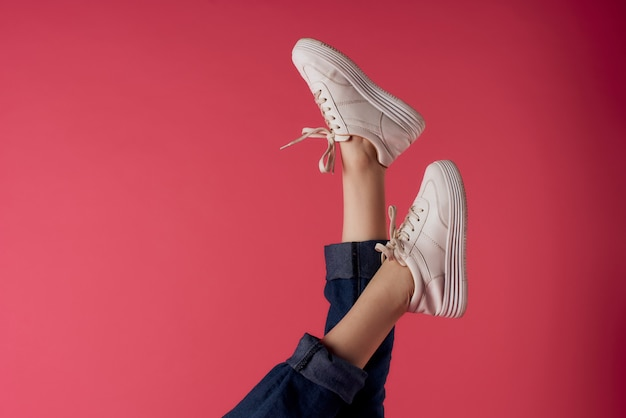 Перевернутые женские ножки в белых кроссовках модная студия на розовом фоне