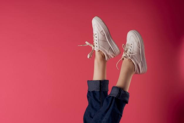白いスニーカーのファッションスタジオで反転した女性の脚