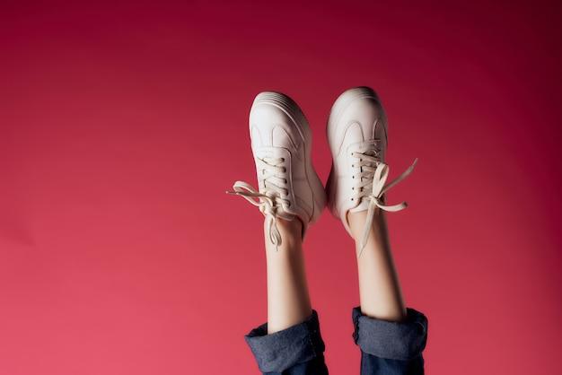 逆さの女性の足のスニーカーのファッションのトリミングされたビュー