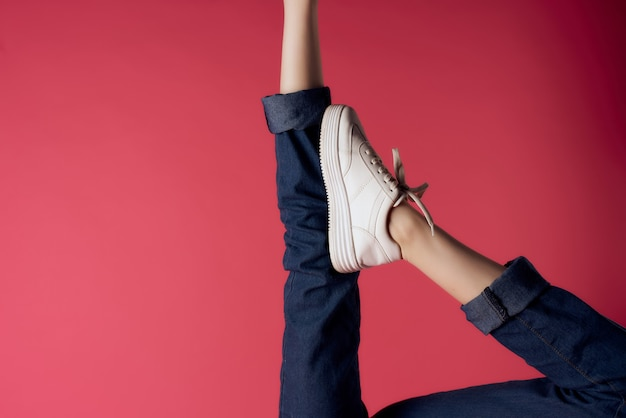 Inverted female legs in white sneakers modern style isolated background