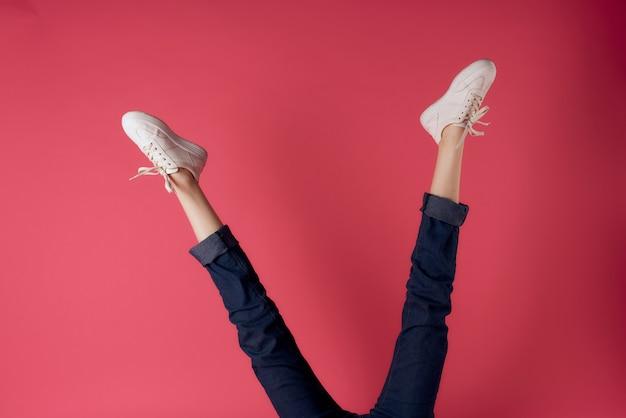 거꾸로 된 여성 다리 흰색 운동화 모션 스트리트 스타일 핑크 배경
