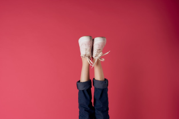 Inverted female legs with white sneakers on red background