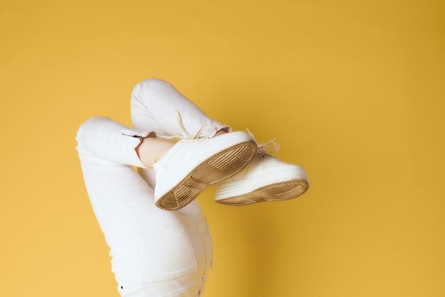 白いスニーカーの逆脚ファッションモダンなスタイルの黄色の背景