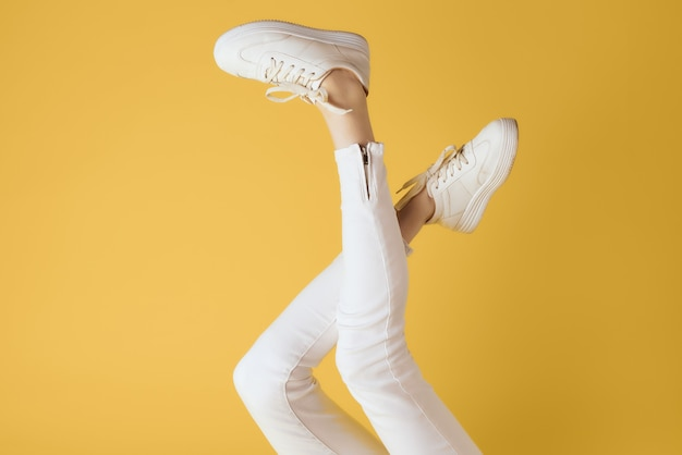 Inverted legs in white sneakers