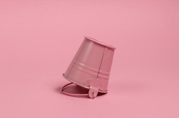 ピンクのパステルカラーの背景のクローズアップの逆ミニバケツ