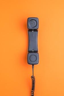 オレンジ色の背景に反転したレトロな電話の携帯電話。フラットレイ。レトロな通信機器。