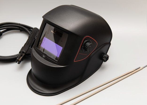 Inverter welding machine, welding equipment, on a gray wall, welding mask, welding electrodes, high-voltage wires with clamps, a set of accessories for arc welding.