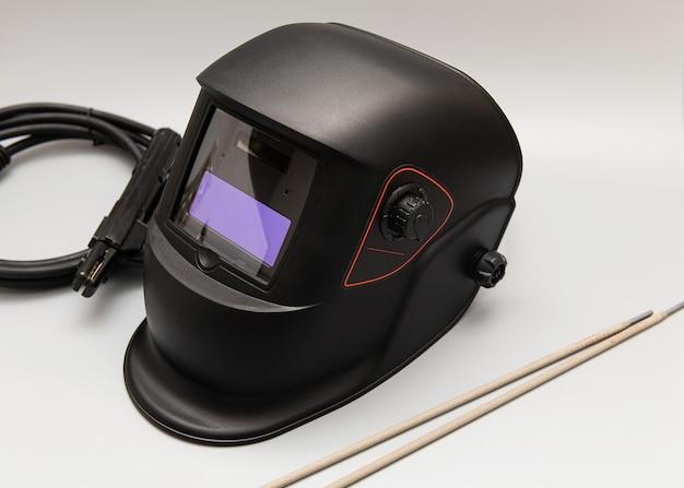 Инверторный сварочный аппарат, сварочное оборудование, на серой стене, сварочная маска, сварочные электроды, высоковольтные провода с зажимами, набор аксессуаров для дуговой сварки.