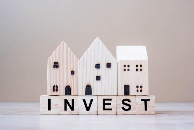 Invest cube blocks with wooden house model on table background.
