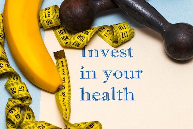 あなたの健康に投資する-ダンベル、バナナ、ルーレットが書かれた紙の碑文
