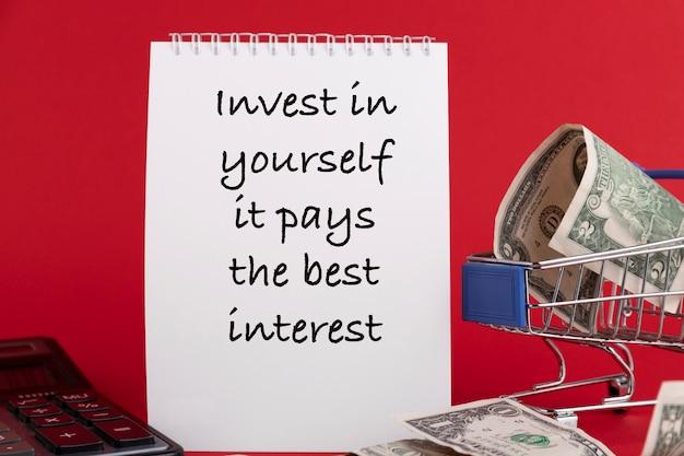 Инвестируйте в себя - это выгоднее всего, текст записан в блокноте белого цвета на красном фоне.