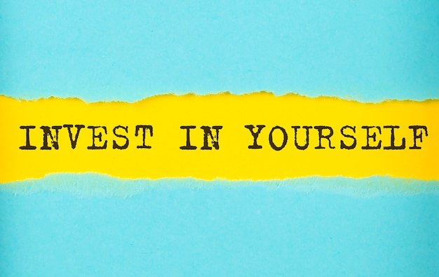 Invest in yourself text on the torn paper , yellow background