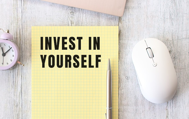 Invest in yourself text written in a notebook lying on a wooden work table next to a laptop