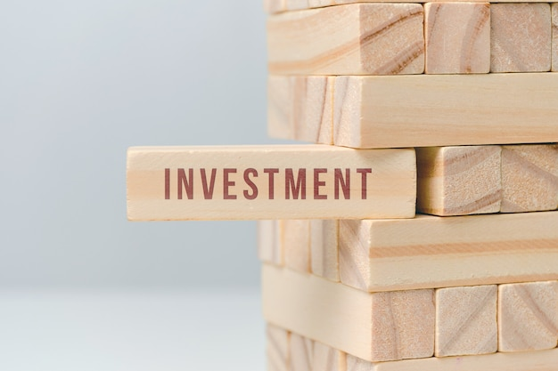 Investment concept - wooden blocks with text on a white space.