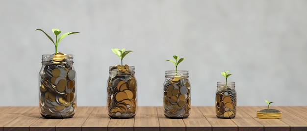 Investment and saving money concept golden coins in glass jars with growing plant on wooden table