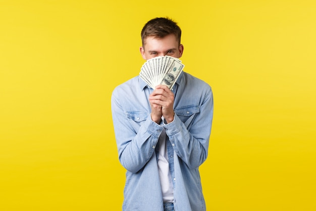 Концепция инвестиций, покупок и финансов. счастливый веселый молодой человек, держащий деньги против лица, выглядывающий счастливыми улыбающимися глазами, чувствуя удовольствие, выигрывая наличные в лотерею, желтый фон.