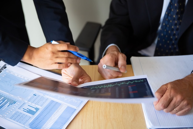 Investor and broker discussing trading strategy, holding papers with financial charts and pens. cropped shot. broker job or investment concept