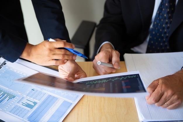 Investitore e broker che discutono la strategia di trading, tenendo in mano documenti con grafici finanziari e penne. colpo ritagliato. lavoro di mediatore o concetto di investimento