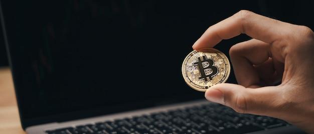 Инвестор бизнесмен, держащий золотой биткойн на темном фоне, торговля, криптовалюта.