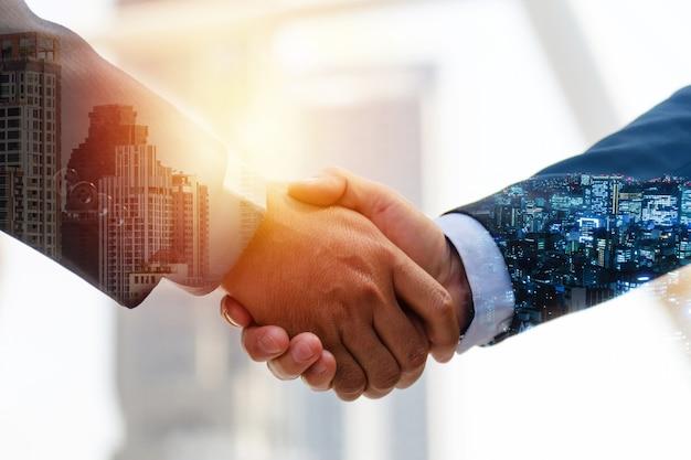 투자자. 일출 및 도시 경관 배경, 투자, 파트너십, 팀워크 개념 동안 성공적인 회의 거래를 위해 파트너와 악수하는 투자자 사업가의 이중 노출 이미지