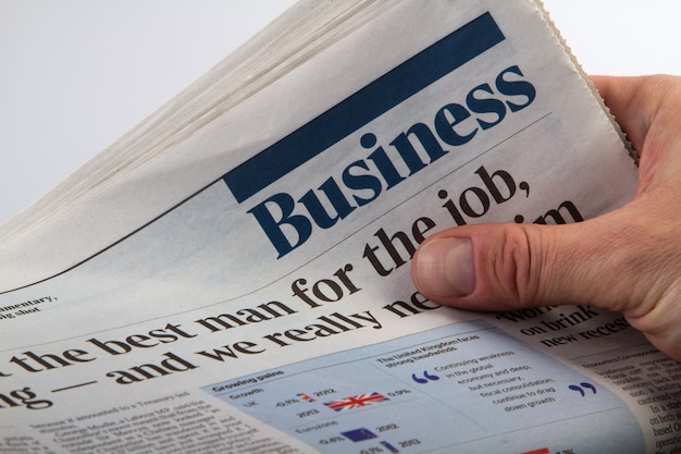 Investor holding and reading business latest newspaper. Premium Photo
